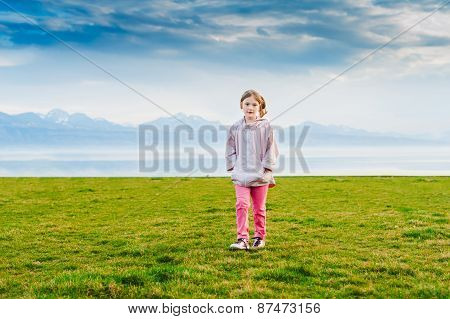 Cute little girl walking by the lake on the sunset