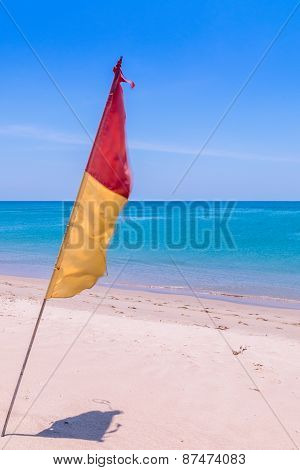 Red And Yellow Flag On The Beach