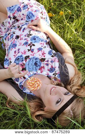 Blonde woman in sundress lying down on grass enjoying summer day