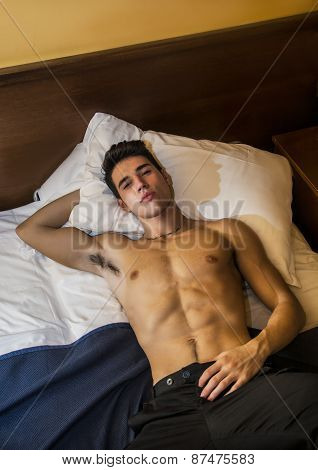 Attractive shirtless athletic young man laying in bed at night