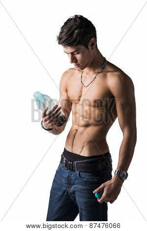 Athletic shirtless young man holding protein shake bottle