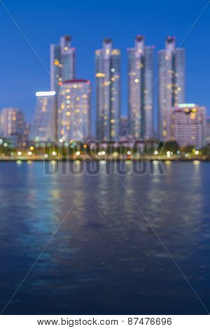 Defocused city lights of modern building background with water reflection