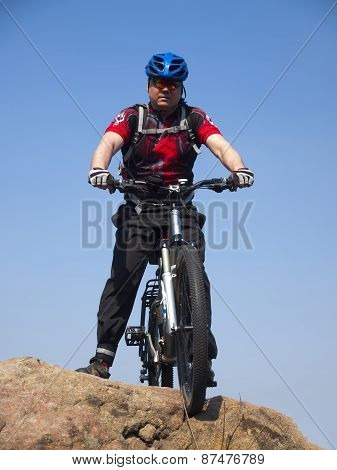 A Man Rides A Bicycle.