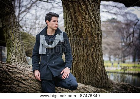 Stylish Man Leaning on Tree Trunk Looking Afar