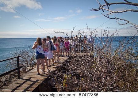 Unidentified tourists enjoying the ocean landscape in view point, San Cristobal, Galapagos Islands
