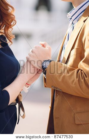 Young beautiful stylish couple in love holding hands on the street