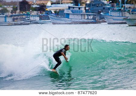 Unidentified man surfing in San Cristobal Island, Galapagos