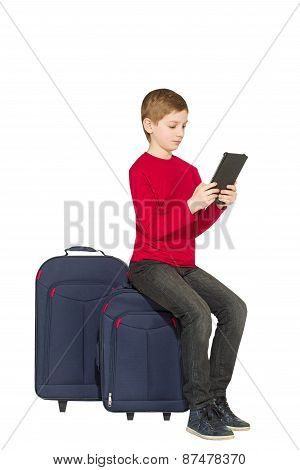 Boy Sitting On Travel Bags With Tablet Pc Isolated On White