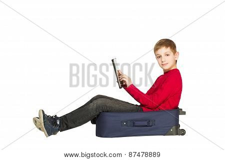 Smiling Boy Sitting In Travel Bag Using Tablet Isolated On White
