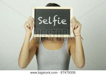 Young Woman Holding A Chalkboard Saying Selfie