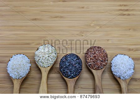 Variety Of Rice In Wood Spoon On Wood Background Showing Unpolished Rice And Polished Rice