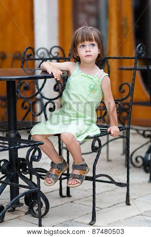 Serious Little Girl Waiting At Coffee Table