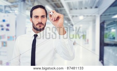Focused businessman writing with marker against college hallway