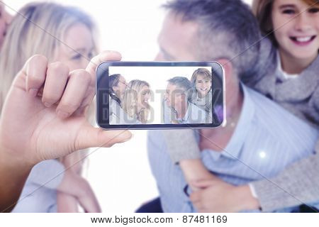 Hand holding smartphone showing against happy two parent giving their children a piggy back