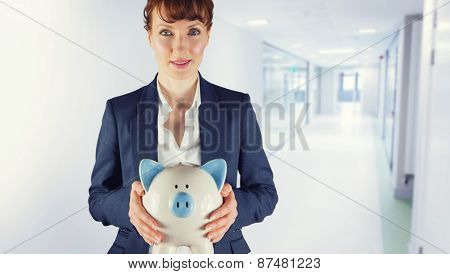 Businesswoman showing piggy bank against college hallway