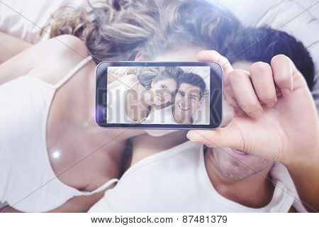 Hand holding smartphone showing against young couple lying in bed at home