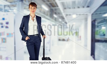 Businesswoman with suitcase against college hallway