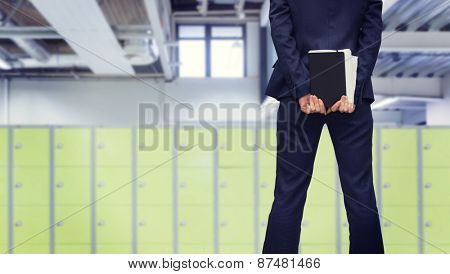 Businesswoman looking against locker room
