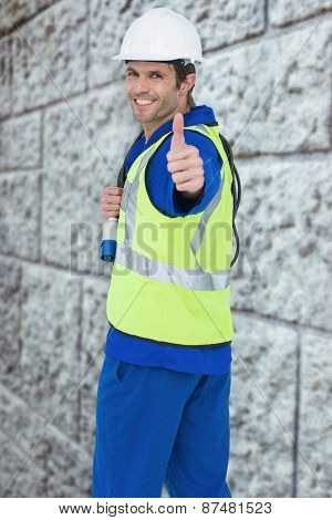 Portrait of happy man showing thumbs up against grey brick wall