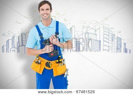 Confident carpenter holding drill machine against grey
