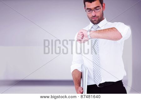 Serious businessman holding laptop checking time against abstract room