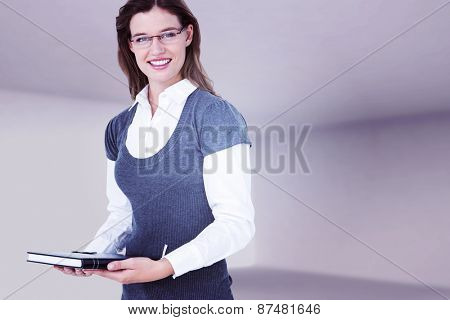 Happy woman holding diary against abstract room