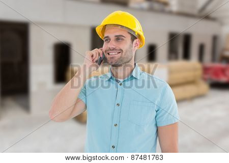 Happy male architect conversing on mobile phone against workshop