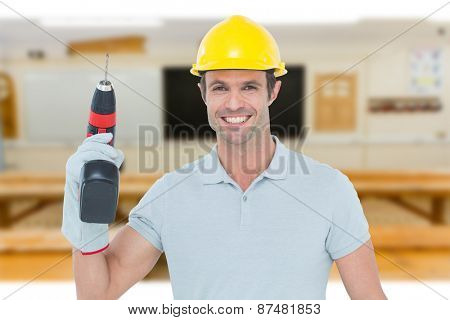 Confident carpenter holding cordless drill machine against workshop