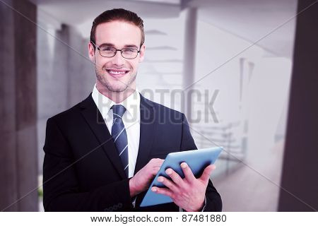 Happy businessman using his tablet pc against stylish modern home interior with staircase