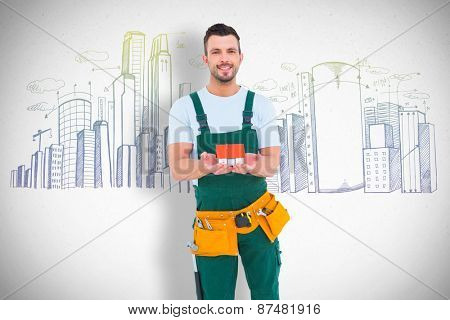 Happy construction worker holding house model against grey