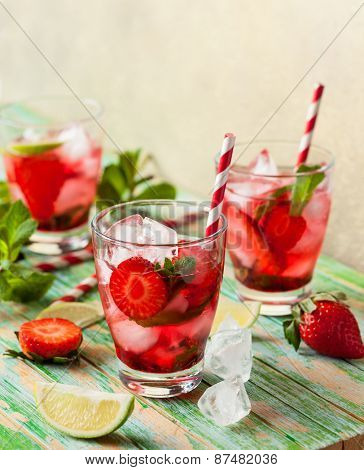 Refreshing summer drink with Strawberry in jug and glasses on the vintage wooden table