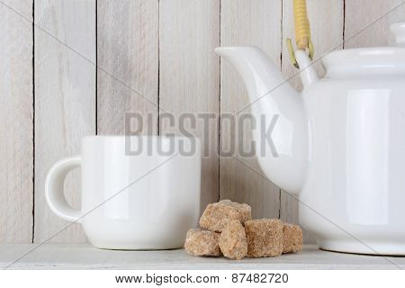 Closeup of natural sugar cubes and a white tea pot and cup on a white wood shelf. Focus is on the sugar.