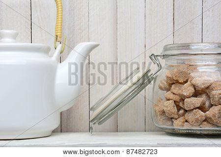 Closeup of a white tea pot and a storage jar full of natural sugar cubes. Horizontal format.