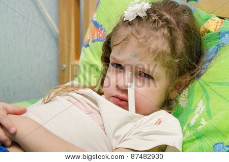Little Girl Lying In Bed With A Thermometer