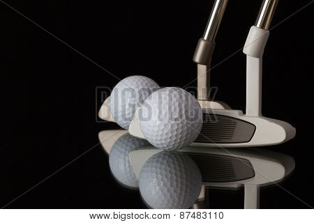 Two Different Golf Putters On A Black Glass Desk