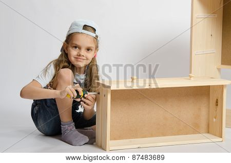 Little Girl In Overalls Collector Collects Furniture Drawer Of The Dresser