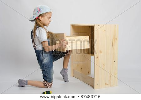 Girl In Overalls Furniture Assembler Inserts A Drawer Chest Of Drawers