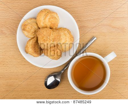 Butter Cookies In White Saucer, Teaspoon And Tea On Table