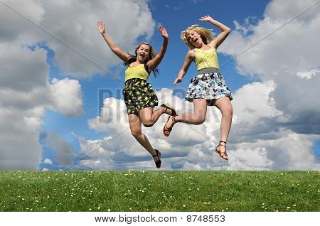 Two Girls Jumping Over Grass Hill