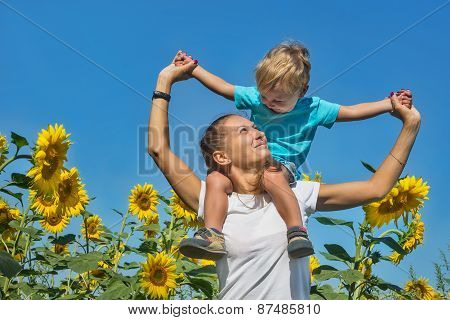Small Son With Mum Among Sunflowers