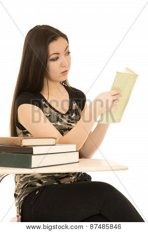 Female Student Sitting At Her Desk Reading Book