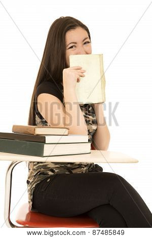 Female Student Sitting At Her Desk Hidding Her Face With Book Smiling