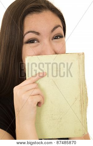 Young Student Laughing Behind A Book Covering Her Face