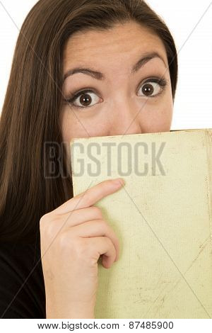 Young Woman With A Surprised Expression Holding A Book Hiding Face
