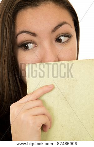 Woman Glancing Sidewards Holding A Book To Her Face