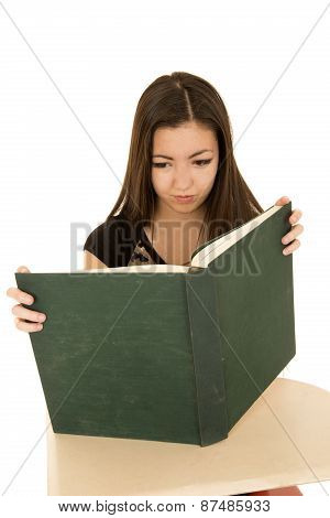 Female Student Reading A Large Book At A School Desk