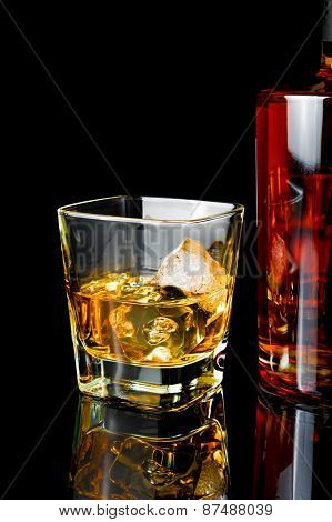 Whiskey With Ice In Glass Near Bottle On Black Background