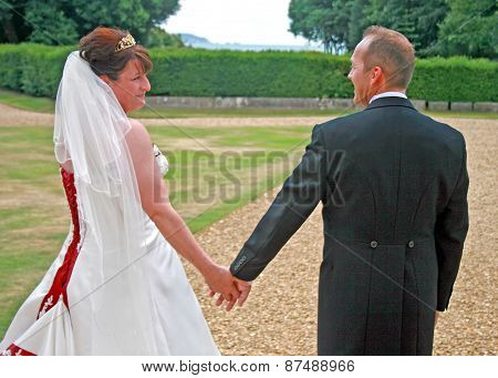 Back Of Bride And Groom Holding Hands