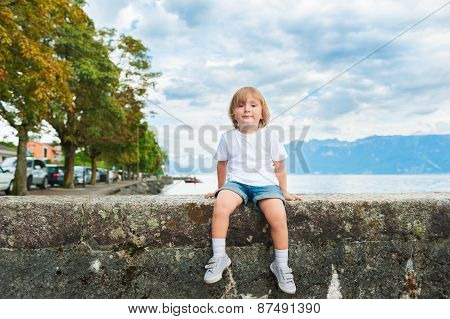 Adorable little boy resting by the lake on a nice summer evening