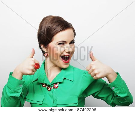 Successful happy girl gives thumb up with two hands